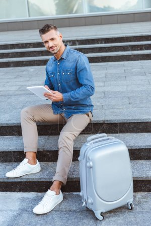 Photo for Handsome adult man using digital tablet and smiling at camera while sitting on the staircase with luggage - Royalty Free Image