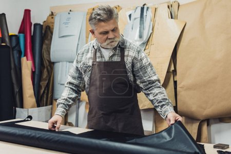 Photo for Mature tailor in apron working with leather at workshop - Royalty Free Image