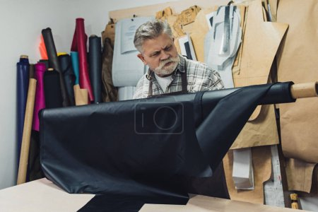 Photo for Focused mature craftsman working with leather at workshop - Royalty Free Image