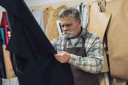 Photo for Concentrated handbag craftsman looking at leather in workshop - Royalty Free Image