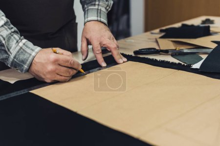 cropped image of handbag craftsman making measurements by pencil and ruler in studio