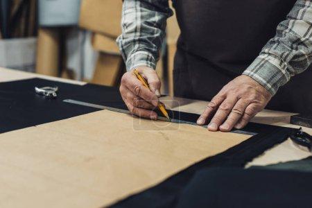 partial view of handbag craftsman making measurements by pencil and ruler in studio