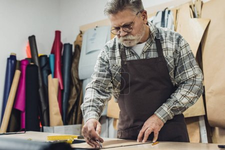 Photo for Focused mature male leather handbag craftsman in apron and eyeglasses working at studio - Royalty Free Image
