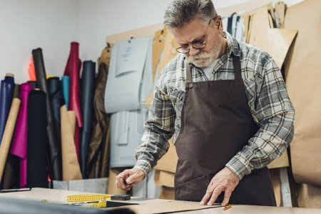 Photo for Selective focus of mature leather handbag craftsman in apron and eyeglasses working at studio - Royalty Free Image