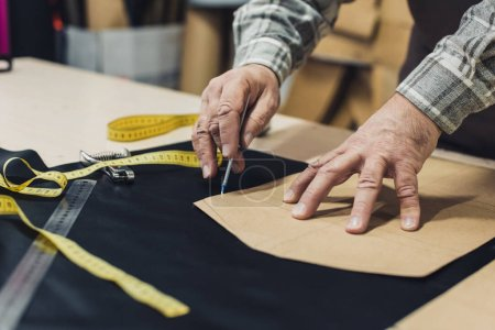 cropped image of male leather handbag craftsman working at studio