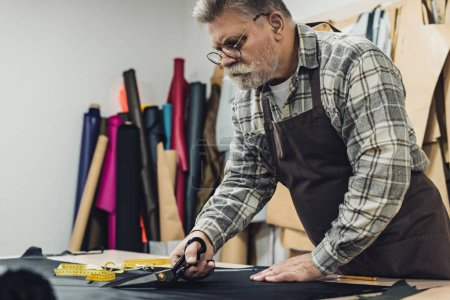 focused handbag craftsman in apron and eyeglasses cutting leather by scissors at workshop