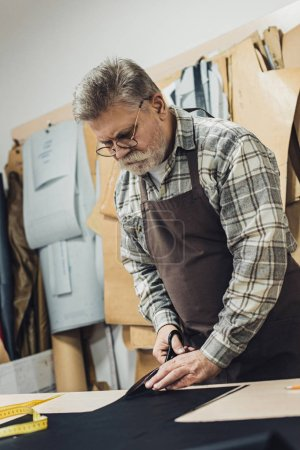 Photo for Mature handbag craftsman in apron and eyeglasses cutting leather by scissors at workshop - Royalty Free Image