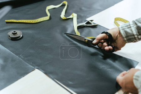 Photo for Cropped image of male handbag craftsman cutting leather by scissors at workshop - Royalty Free Image