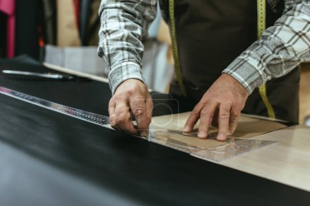 Photo for Cropped image of handbag craftsman making measurements on leather at workshop - Royalty Free Image