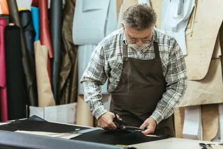 middle aged male handbag craftsman in apron and eyeglasses cutting leather by scissors at workshop