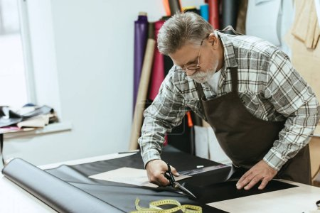 Photo for Male craftsman in apron and eyeglasses cutting leather by scissors at workshop - Royalty Free Image