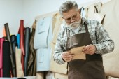 focused middle aged handbag craftsman in apron and eyeglasses working at studio