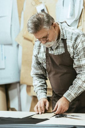 serious middle aged handbag craftsman in apron and eyeglasses working at studio