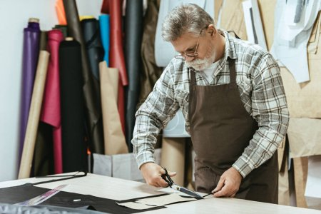Photo for Concentrated male handbag craftsman in apron and eyeglasses cutting leather by scissors at workshop - Royalty Free Image