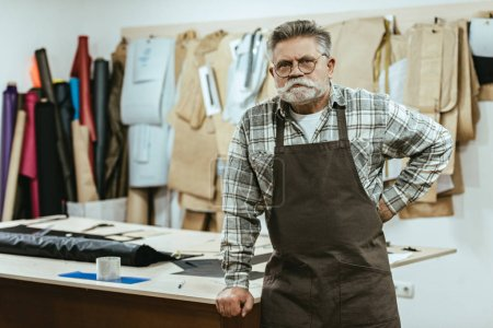 Photo for Confident male craftsman in apron and eyeglasses posing at studio - Royalty Free Image