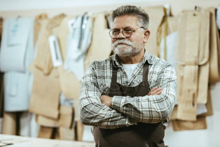 Photo for Happy middle aged craftsman in apron and eyeglasses standing with crossed arms at studio - Royalty Free Image