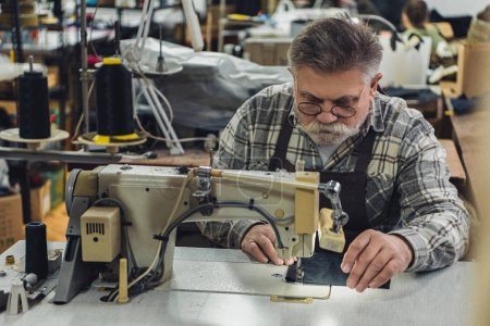 middle aged tailor in apron and eyeglasses working on sewing machine at studio