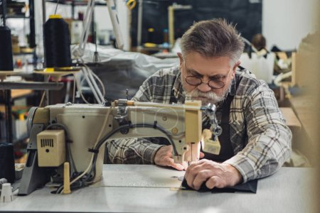 Photo for Focused mature male tailor in apron and eyeglasses working on sewing machine at studio - Royalty Free Image