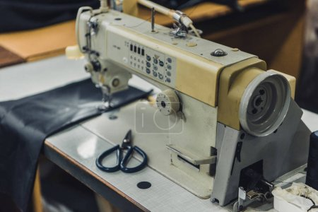 selective focus of tailor workplace with sewing machine at workshop