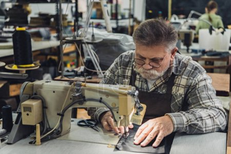 serious mature male tailor in apron and eyeglasses working on sewing machine at studio