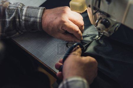 Photo for Cropped image of male handbag craftsman cutting leather near sewing machine at studio - Royalty Free Image