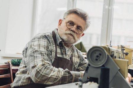 Foto de Retrato de sastre masculino maduro en delantal y anteojos sentado junto a la máquina de coser en estudio - Imagen libre de derechos