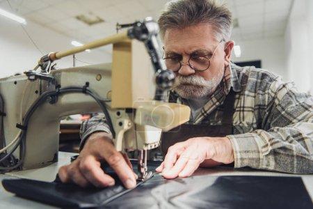Foto de Enfoque selectivo de sastre masculino maduro en delantal y anteojos trabajando en máquina de coser en estudio - Imagen libre de derechos