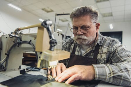 Foto de Sastre masculino maduro concentrado en delantal y anteojos trabajando en máquina de coser en estudio - Imagen libre de derechos