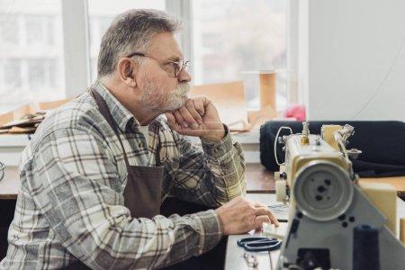 Photo pour Vue latérale du songeur tailleur mâle mature en tablier et lunettes assis près de la machine à coudre au studio - image libre de droit
