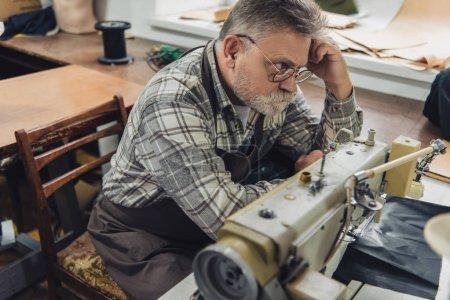 Photo pour Vue sur un angle élevé de tailleur mâle mature à tablier et lunettes assis près de la machine à coudre au studio - image libre de droit