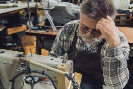 Photo pour Mise au point sélective de mature tailleur masculin en tablier et lunettes assis près de la machine à coudre au studio - image libre de droit