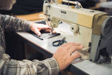 cropped image of male tailor working on sewing machine at studio