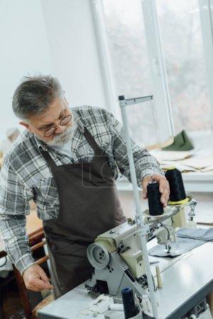 Photo pour Porté milieu tailleur âgé dans les chaînes de paramètre tablier sur machine à coudre à l'atelier - image libre de droit