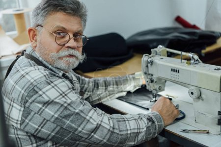 Photo for Portrait of mature male tailor in apron and eyeglasses sitting near sewing machine at studio - Royalty Free Image