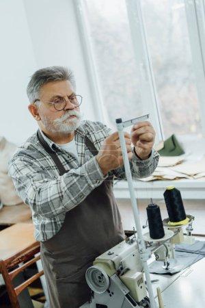 Foto de Enfocado sastre edad media en las cadenas de corte delantal de máquina de coser en taller - Imagen libre de derechos