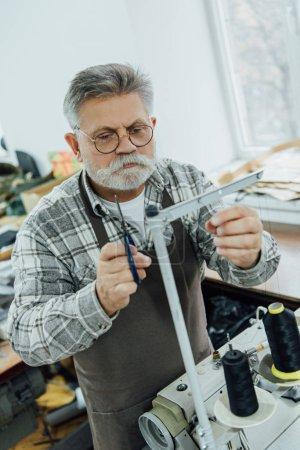 Photo pour Un angle élevé Découvre des mature tailleur masculin dans les chaînes de mise en tablier sur machine à coudre à l'atelier - image libre de droit