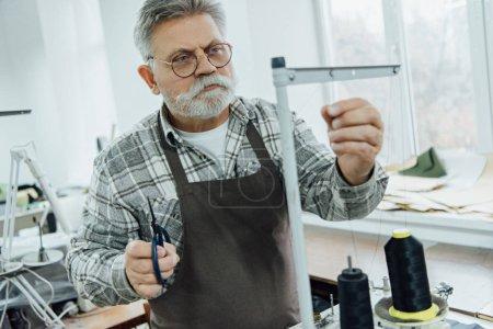 Photo pour Axé mature tailleur masculin dans les chaînes de paramètre tablier sur machine à coudre à l'atelier - image libre de droit