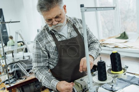 Photo for Selective focus of mature male tailor in apron setting strings on sewing machine at workshop - Royalty Free Image