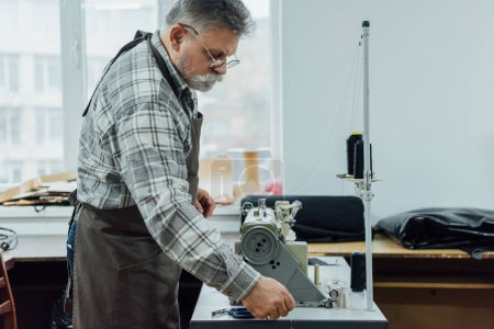 Photo for Side view of mature male tailor in apron setting strings on sewing machine at workshop - Royalty Free Image