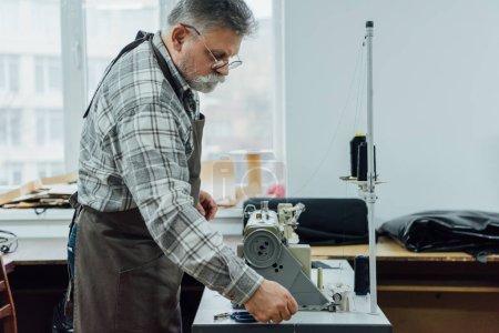 Photo pour Vue de côté de mature tailleur masculin dans les chaînes de paramètre tablier sur machine à coudre à l'atelier - image libre de droit