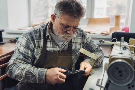 Photo pour Mature tailleur mâle à lunettes et du tablier coupe cuir de ciseaux à l'atelier - image libre de droit