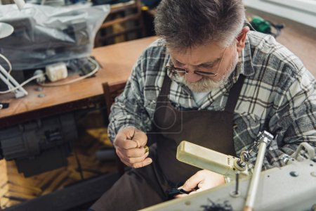 high angle view of middle aged male tailor in eyeglasses and apron sewing at workshop