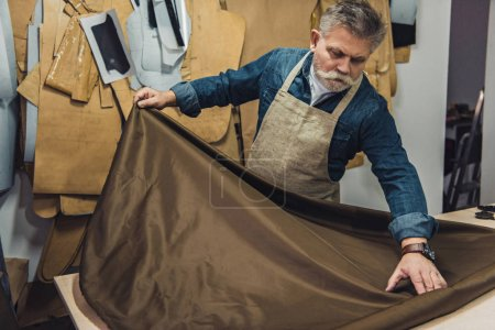 Photo for Middle aged male handbag craftsman putting fabric on working table at studio - Royalty Free Image