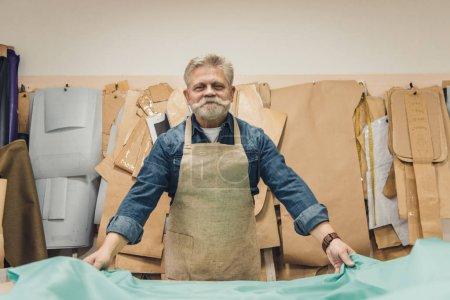 cheerful mature male handbag craftsman putting fabric on working table at studio