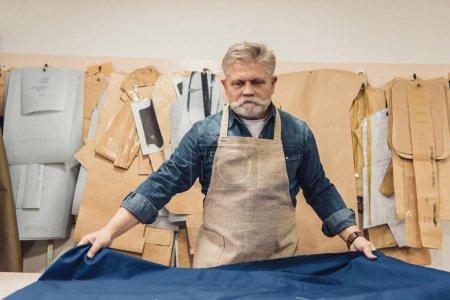artisan mâle moyen ans sac à main, mettre le tissu sur la table de travail au studio