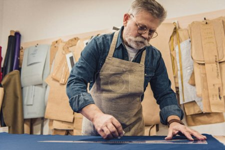 Photo for Low angle view of male middle aged craftsman in apron making measurements on fabric at workshop - Royalty Free Image