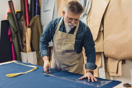 focused middle aged male craftsman in apron making measurements on fabric at workshop