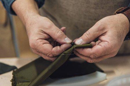 cropped image of male handbag craftsman working at studio