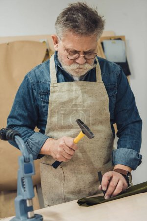serious middle aged male handbag craftsman working with hammer at studio