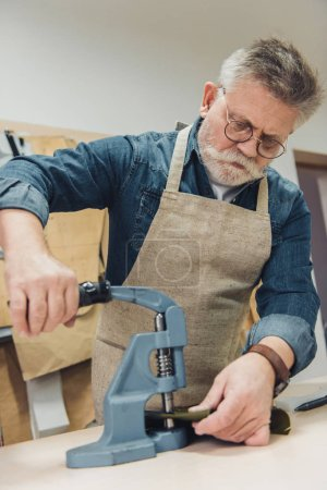 focused male handbag craftsman working with tool at studio